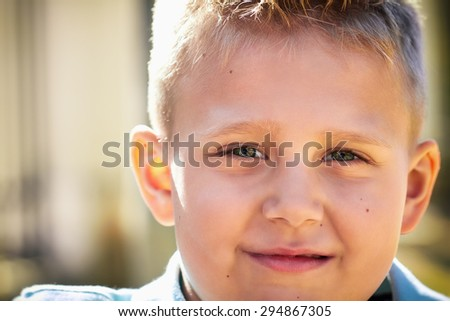 Outdoor portrait of a small boy. Smiling blonde little boy. - stock photo