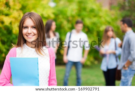 Outdoor portrait of a smiling student - stock photo