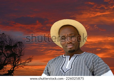 Outdoor portrait of a South African black man with friendly smiling facial expression on a red sky sunrise background. - stock photo