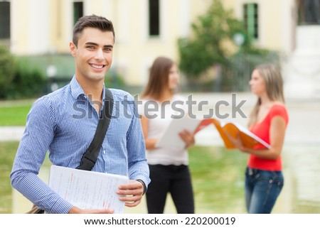 Outdoor portrait of a student in front of his school - stock photo