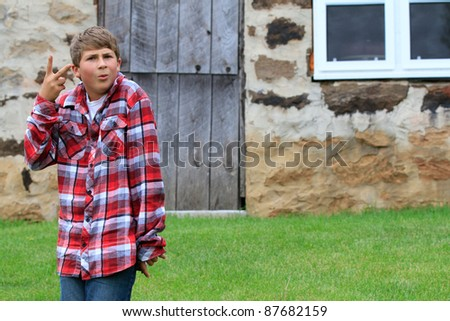 Outdoor portrait of a teenager standing in front of a barn stone wall - stock photo