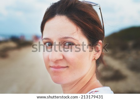 outdoor portrait of a thirty-something woman looking at the camera  - stock photo
