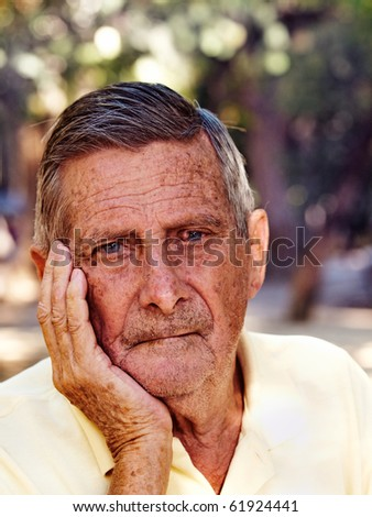 outdoor portrait of a thoughtfully old man - stock photo