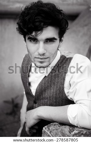 outdoor portrait of a very beautiful sexy young man, dark hair, posing in an old courtyard in classic suit  - stock photo