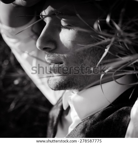 outdoor portrait of a very beautiful sexy young man, dark hair, posing in the grass in classic suit  - stock photo