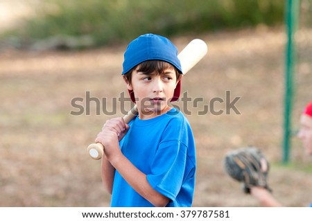 Outdoor portrait of a young baseball kid in blue shirt looking serious and sideways holding a wooden bat. - stock photo