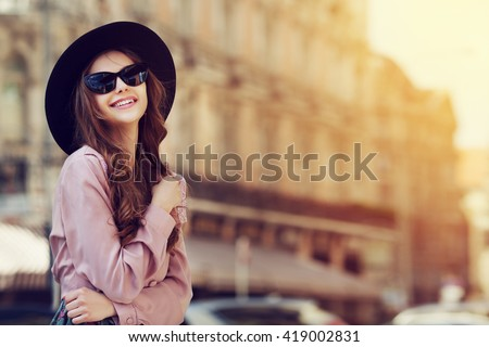 Outdoor portrait of a young beautiful fashionable happy lady posing on a street of the old city. Model wearing stylish clothes. Girl looking up. Female fashion. City lifestyle. Copy space for text - stock photo