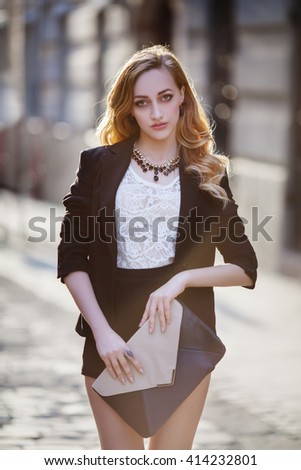 Outdoor portrait of a young beautiful fashionable lady posing on a street of the old city. Model wearing stylish clothes. Girl looking at camera. Female fashion concept. City lifestyle.  - stock photo