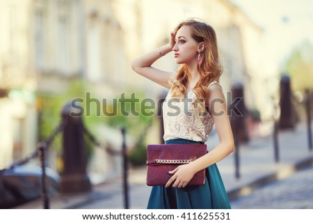 Outdoor portrait of a young beautiful fashionable lady walking posing on a street of the old city. Model wearing stylish clothes. Girl looking aside. Female fashion concept. City lifestyle. - stock photo