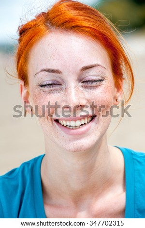 Outdoor portrait of a young beautiful redhead freckled woman smiling happily with her eyes closed.