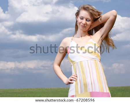 Outdoor portrait of a young lady on a blue cloudy sky background