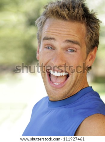 Outdoor portrait of a young man with big fun expression laughing
