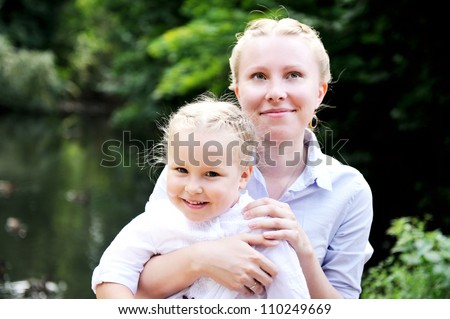 Outdoor portrait of a young mother posing with her daughter in the park - stock photo