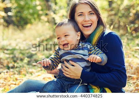 outdoor portrait of a young mother with her baby. Mom and son