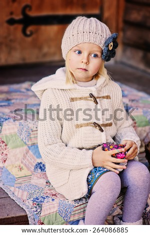 outdoor portrait of adorable child girl in beige knitted hat and coat