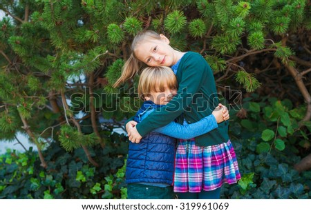 Outdoor portrait of adorable fashion kids in schoolwear - stock photo