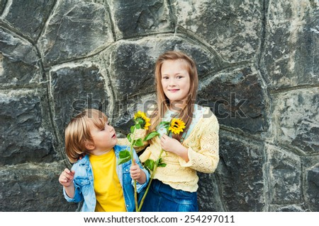 Outdoor portrait of adorable kids holding sunflowers - stock photo