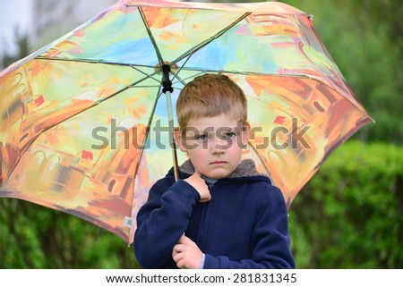 Outdoor portrait of adorable little blond boy with umbrella under the rain - stock photo