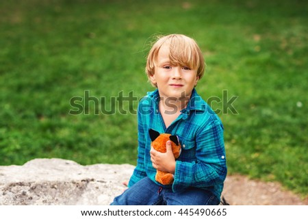 Outdoor portrait of adorable little boy of 4 years old playing in the park with a fox toy on a nice day, wearing emerald shirt - stock photo