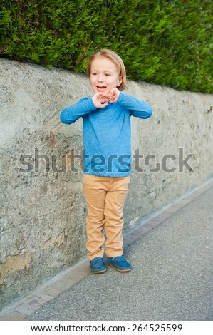 Outdoor portrait of adorable little boy wearing blue t-shirt, beige trousers and dark blue moccasins - stock photo
