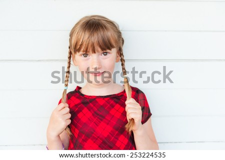 Outdoor portrait of adorable little girl against white wooden background - stock photo