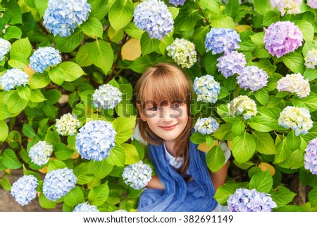 Outdoor portrait of adorable little girl of 6-7 years old, sitting between beautiful blue hydrangea flowers, covering with purple scarf - stock photo