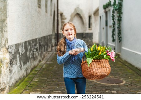 Outdoor portrait of adorable little girl of 7 years old walking in old town, holding basket full of colorful tulips, wearing warm blue pullover and scarf - stock photo
