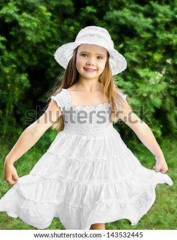 Outdoor portrait of adorable smiling little girl in white dress and hat - stock photo