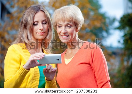 Outdoor portrait of Adult daughter showing on mobile phone to her senior mother outdoor in nature - stock photo