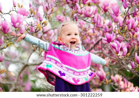 Outdoor portrait of an adorable happy little toddler girl wearing warm knitted poncho, tights and boots enjoying sunshine on a beautiful spring day in the garden with magnolia trees in full bloom - stock photo