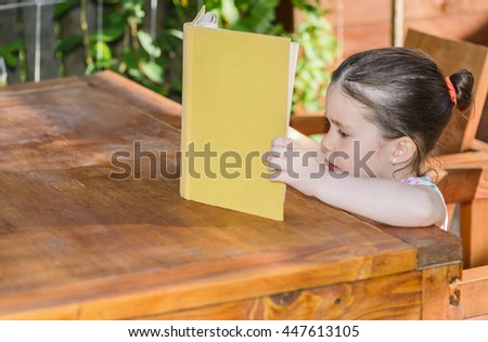 Outdoor portrait of an adorable young little girl reading a book sitting on a wooden table in backyard - stock photo