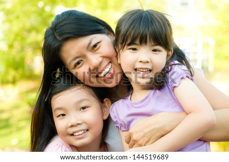 Outdoor portrait of asian mother and daughters - stock photo
