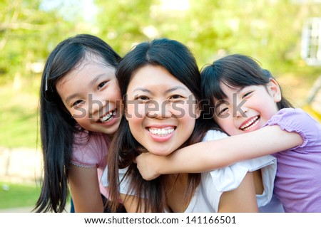 Outdoor portrait of asian mother and her lovely daughters - stock photo