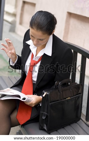 outdoor portrait of attractive young businesswoman reading magazine - stock photo