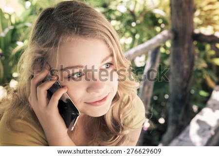 Outdoor portrait of beautiful blond smiling Caucasian teenage girl in a park talking on a cell phone, vintage toned photo filter effect, instagram style - stock photo