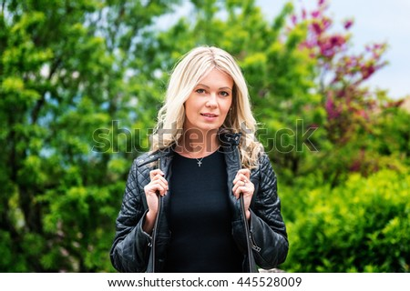 Outdoor portrait of beautiful blond woman wearing black leather jacket
