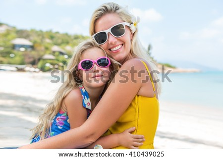 Outdoor portrait of beautiful blonde mother and her cute daughter. Small girl and her mammy look to the camera on the beach. Little lady and mom wearing sunglasses. Summer sunny day Happy Mothers day.
