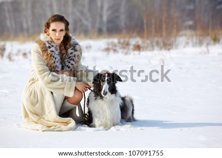 outdoor portrait of beautiful brunette woman in fur coat with borzoi in snowy filed with winter forest on background