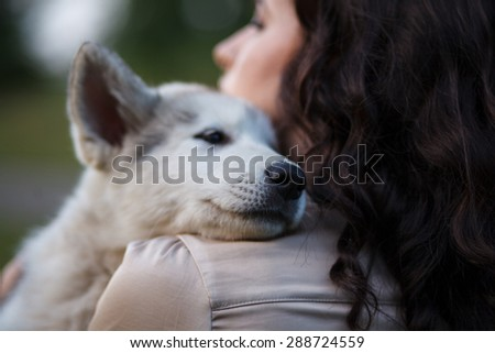 Outdoor portrait of beautiful girl and malamute pup - stock photo