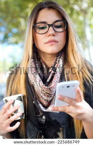 Outdoor portrait of beautiful girl drinking coffee and using her mobile phone in city. - stock photo