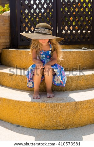 Outdoor portrait of beautiful girl in floral dress and beach straw hat. She sit on stairs and look down. Wind waves her blonde hair. Summer day. Wooden fence at tropical background. Mothers day. - stock photo