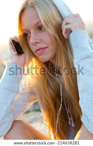 Outdoor portrait of beautiful girl sitting on the roof and listening to music.