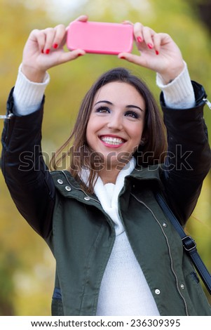 Outdoor portrait of beautiful girl taking a selfie in autumn. - stock photo