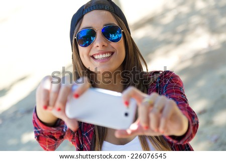 Outdoor portrait of beautiful girl taking a selfie with mobile phone in city. - stock photo