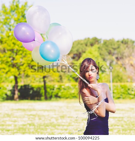 Outdoor portrait of beautiful girl with balloons.
