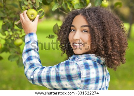 Outdoor portrait of beautiful happy mixed race African American girl teenager female child young woman picking an organic green apple in an orchard and smiling with perfect teeth