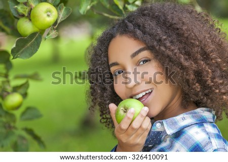 Outdoor portrait of beautiful happy mixed race African American girl teenager female young woman child eating an organic green apple and smiling with perfect teeth - stock photo