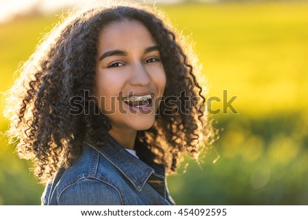 Outdoor portrait of beautiful happy mixed race African American girl teenager female young woman smiling laughing with perfect teeth in field of yellow flowers - stock photo