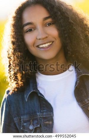 Outdoor portrait of beautiful happy mixed race African American girl teenager female young woman smiling laughing with perfect teeth in golden evening sunshine
