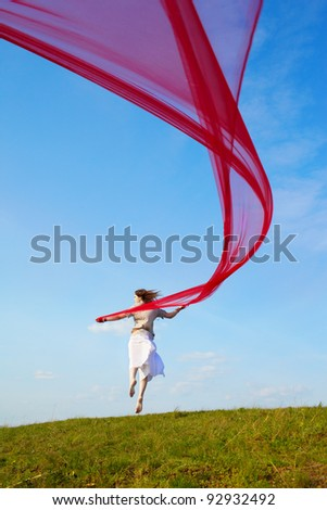 outdoor portrait of beautiful hippie girl jumping with big piece of red light cloth under the blue sky